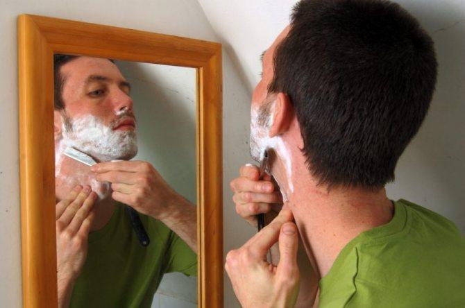 мужчина бреется перед зеркалом